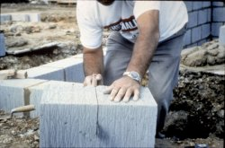 Photo of a man sawing a concrete block