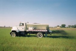 Photo of a truck applying wood ash residual to a field