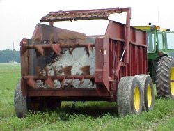 Photo of agricultural machinery applying wood and paper residue to a field